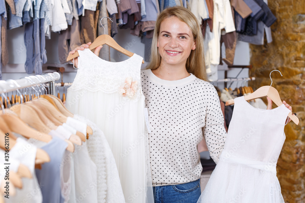 Fototapeta Positive young woman searching baby white dress in kids clothes store