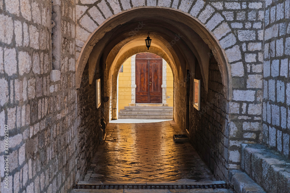 Stone gate under the cathedral tower in the old town of Krk on the island of Krk in Croatia