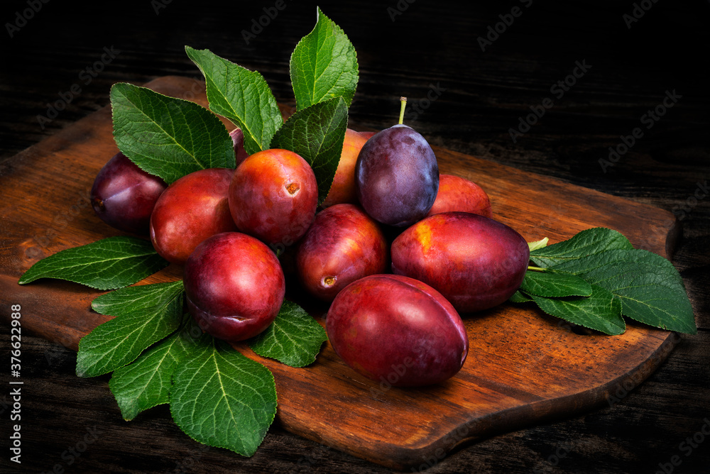 Fototapeta Ripe juicy plums with leaves on a cutting board wooden background.