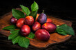 Ripe juicy plums with leaves on a cutting board wooden background.