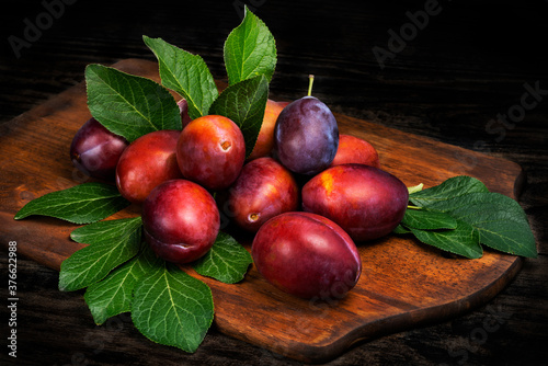 Obraz Ripe juicy plums with leaves on a cutting board wooden background. - fototapety do salonu