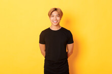 Portrait Of Friendly Handsome Asian Guy With Blond Hair, Smiling Politely, Holding Hands Behind Back, Standing Yellow Background