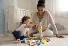 Happy Young African American Mother Or Nanny Sitting On Floor Carpet, Constructing Building With Wooden Cubes With Curious Adorable Small Toddler Baby Boy Girl In Children Room, Childcare Concept.