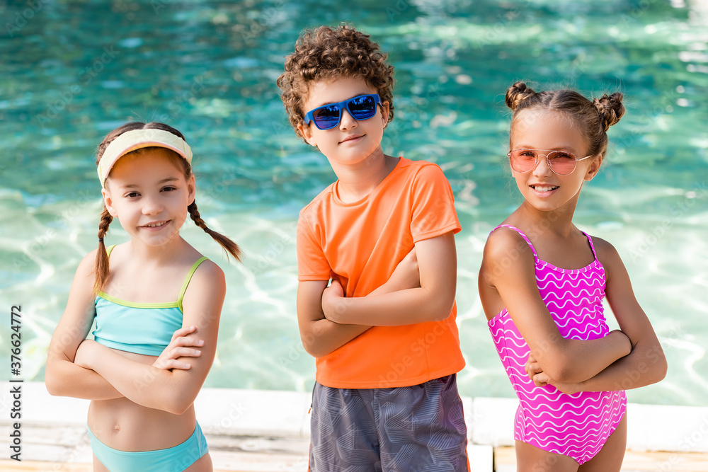 Fototapeta girls in swimsuits and curly boy in sunglasses standing with crossed arms near pool