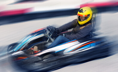 Young woman in helmet driving car for karting in sport club outdoor
