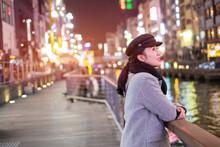 Beautiful Smiling Woman Tourists Traveling In Walking At Street Shopping Center Dotonbori In Osaka, Japan.