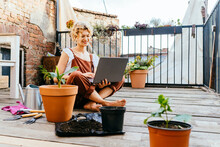 Blond Woman Gardener Wear Brown Overalls, Sitting On Wooden Floor In Terrace Resting, Using Laptop After Work, Smiling And Speaking On Video Call Surrounded By Plants. Home Gardening Concept.