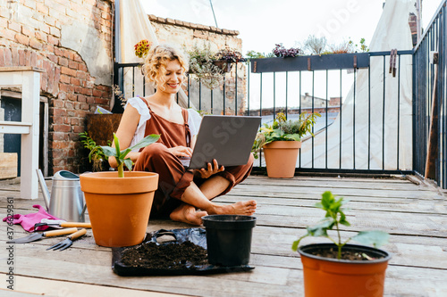 Leinwand Poster Blond woman gardener wear brown overalls, sitting on wooden floor in terrace resting, using laptop after work, smiling and speaking on video call surrounded by plants
