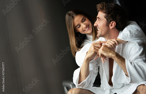 Happy young couple in white bathrobes drinking coffee together Canvas
