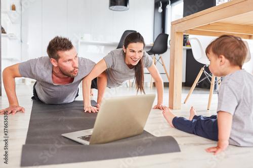 Sportliche Eltern machen Sport vor dem Laptop #376636305