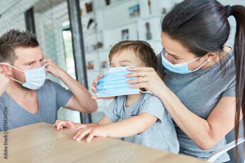Eltern befestigen Mundschutz bei ihrem Sohn Canvas Print