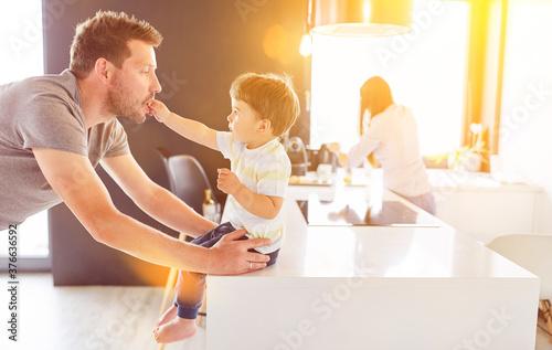 Vater spielt mit Kind in Küche zu Hause #376636592