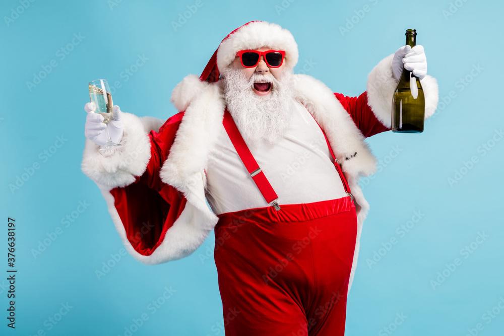 Fototapeta Photo of retired old man grey beard funky hold bottle full glass golden wine drink having fun open mouth wear santa x-mas costume suspender sunglass cap isolated blue color background