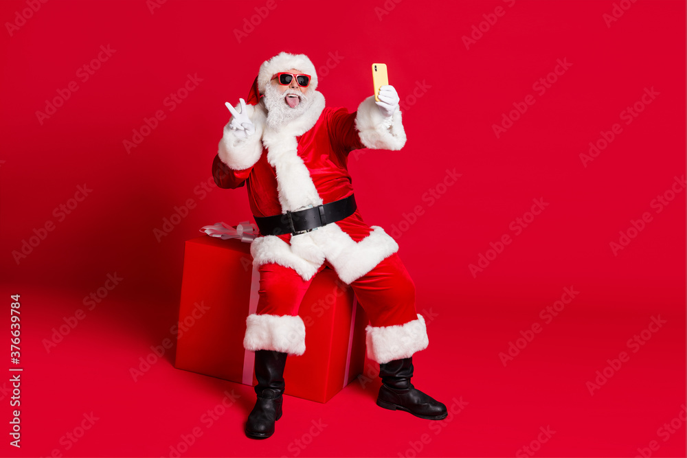Fototapeta Photo of retired old man white beard sit giftbox show v-sign make selfie portrait stick-out tongue wear x-mas santa costume glove coat belt sunglass cap boot isolated red color background