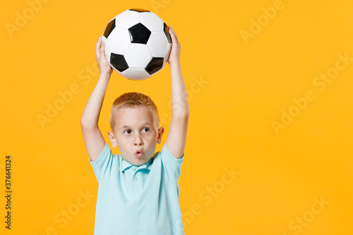 Photo Fun inspired little kid boy 5-6 years old football fan in blue t-shirt cheer up support favorite team, hold in hands soccer ball isolated on yellow background