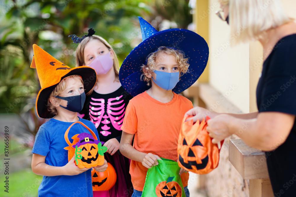 Fototapeta Kids trick or treat. Halloween in face mask.