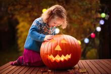 Little Girl Carving Pumpkin At...