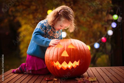 Little girl carving pumpkin at Halloween Canvas Print