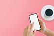 Leinwandbild Motiv Black smartphone with white blank screen in hand on pink background.