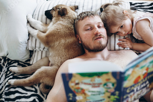 Foto A man of European appearance reads a book for a night a girl of three years