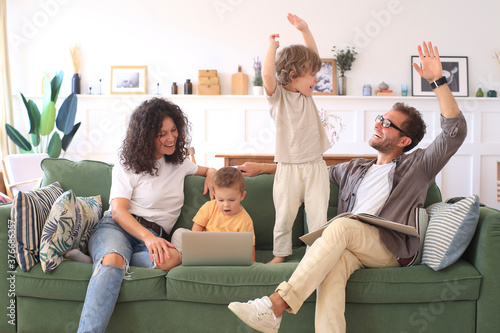 Fotografie, Tablou Young beautiful happy family relaxing on the sofa and look at the laptop at home