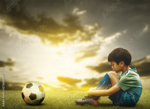 Tablou Canvas Sad soccer kid sitting on a field with soccer ball godlen sky for disappointment in Foot ball sport playing