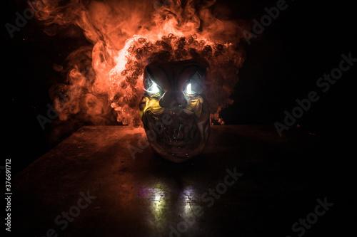 Fotografie, Obraz Spooky Clown head on wooden table