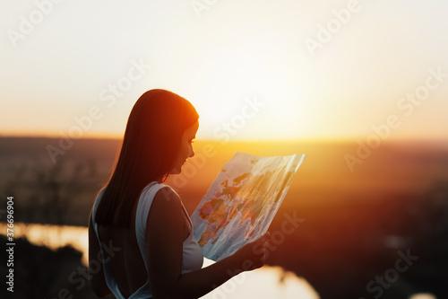 Fotografija Traveler girl looking right direction on map, bright orange sunset light