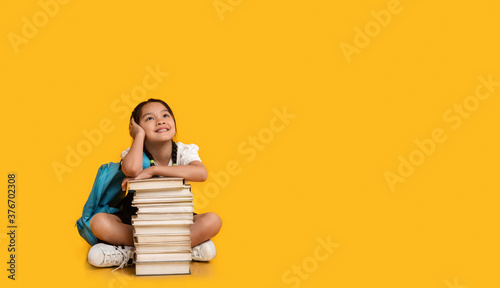 Chinese School Girl Sitting At Books Stack On Yellow Background Canvas