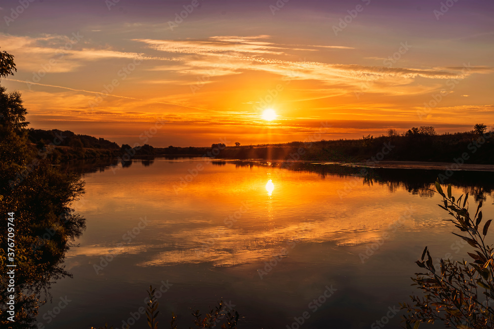 Fototapeta Scenic view at beautiful summer river sunset with reflection on water with green bushes, grass, golden sun rays, calm water ,deep blue cloudy sky and glow on a background, spring evening landscape