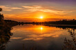 Scenic view at beautiful summer river sunset with reflection on water with green bushes, grass, golden sun rays, calm water ,deep blue cloudy sky and glow on a background, spring evening landscape