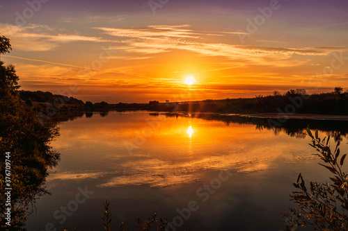 Fototapeta Scenic view at beautiful summer river sunset with reflection on water with green bushes, grass, golden sun rays, calm water ,deep blue cloudy sky and glow on a background, spring evening landscape obraz