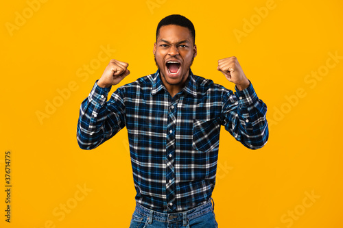 Photographie Emotional African Man Shouting Loudly Shaking Fists Over Yellow Background