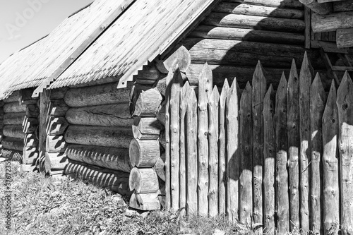 Obraz na plátně An old hut made of thick logs and a wooden palisade.