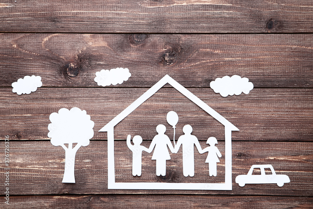 Paper family figures with tree and house on brown wooden table