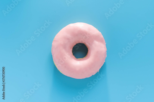 Fotografie, Obraz Donut covered with pink strawberry cream are placed on a pastel blue background
