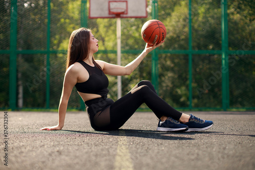 Attractive young athletic girl, outdoors, posing with a basketball. Sport, fashion
