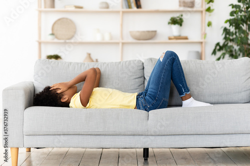 Frustrated Black Girl Crying Covering Face Lying On Couch Indoor Fototapeta