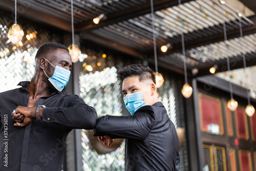 Canvas Print African American black man and Asian friend wearing protective face mask elbow bump greeting for social distancing and new normal business etiquette to prevent Coronavirus infection