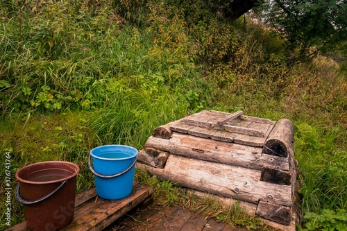 Fotomural Rural retro landscape with wooden well and buckets of water on a hillside with g