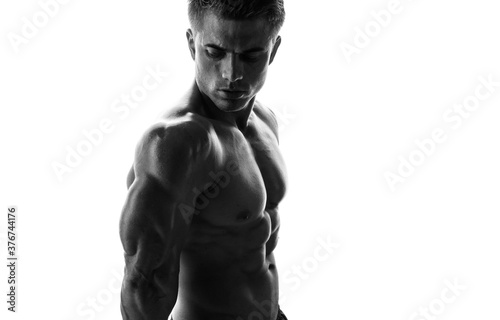 Fototapeta Muscular model sports young man on white background. Black and white fashion portrait of strong brutal guy. Sexy torso. Male flexing his muscles. obraz na płótnie