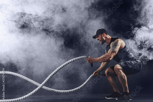 Fototapeta Bearded athletic looking bodybulder work out with battle rope on dark studio background with smoke