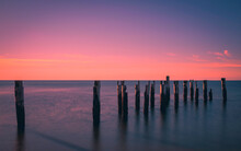 Tranquil Seascape With Ruined Pilings Of The Pier In The Seawater. Warm Glowing Pink Sunrise Over Blue Water. Long Exposure Image.