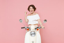 Happy Joyful Young Brunette Woman 20s In White Summer Clothes Clenching Fist Doing Winner Gesture Keeping Eyes Closed Sitting Driving Moped Isolated On Pastel Pink Colour Background, Studio Portrait.