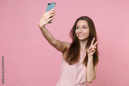 Fotografía Smiling beautiful young brunette woman 20s wearing pink summer dotted dress posing doing selfie shot on mobile phone showing victory sign isolated on pastel pink color wall background studio portrait