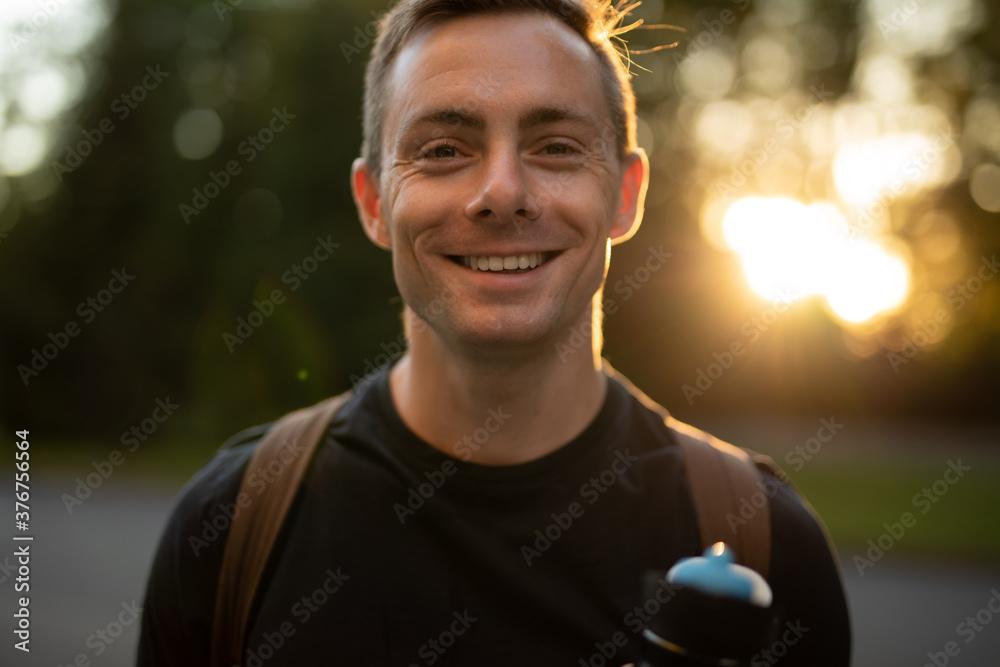 Fototapeta Young man smiling at the camera in park