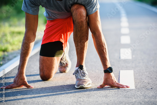 Sports man runner with smart watch in start position preparing to run Canvas