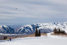 Three People Flying A Kite In Winter Landscape, Eden, Utah, USA