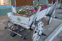 An Old Antique Cart In White, Filled With Flowers.