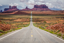 View Of Empty Road Leading To Monument Valley